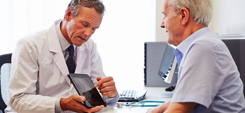 """Older man sitting with physician wondering """"what are good questions to ask my doctor after a car accident?"""""""