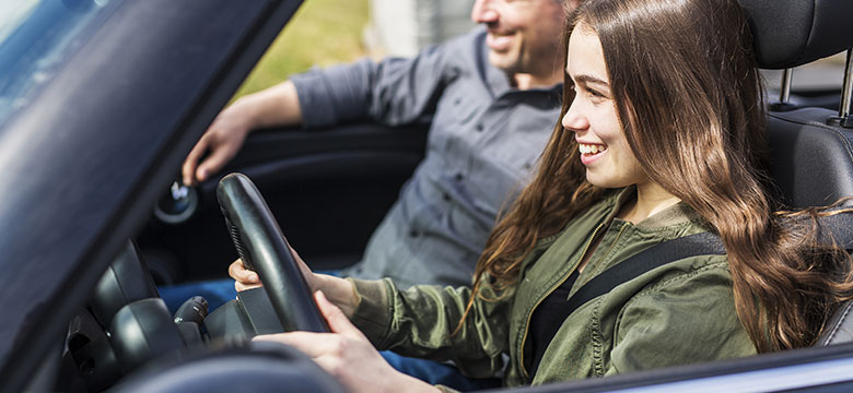 Father teaching teenage daughter how to be a safe driver